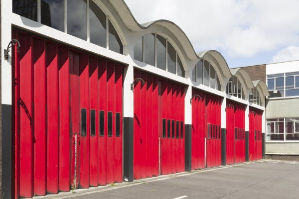 Red concertina-type folding garage doors at a redundant fire station in England
