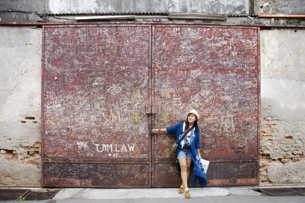 Thai woman travel and portrait with dirty Iron steel red door ol