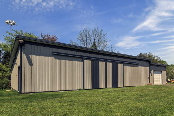 Long steel and modern barn with closed sliding doors and garage addition. Blue sky in the background.