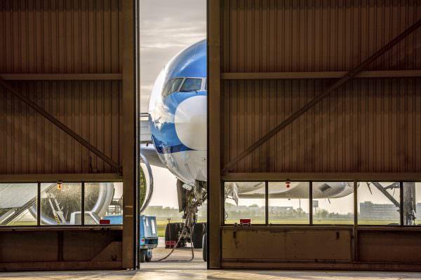 Blue airplane in front of half opened door to hangar