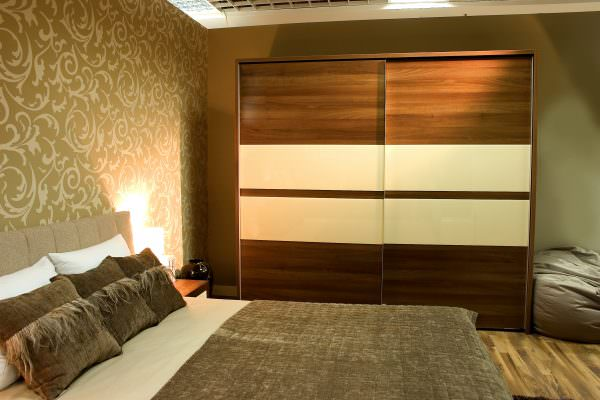 Modern bedroom with brown wardrobe and bed with two pillows.